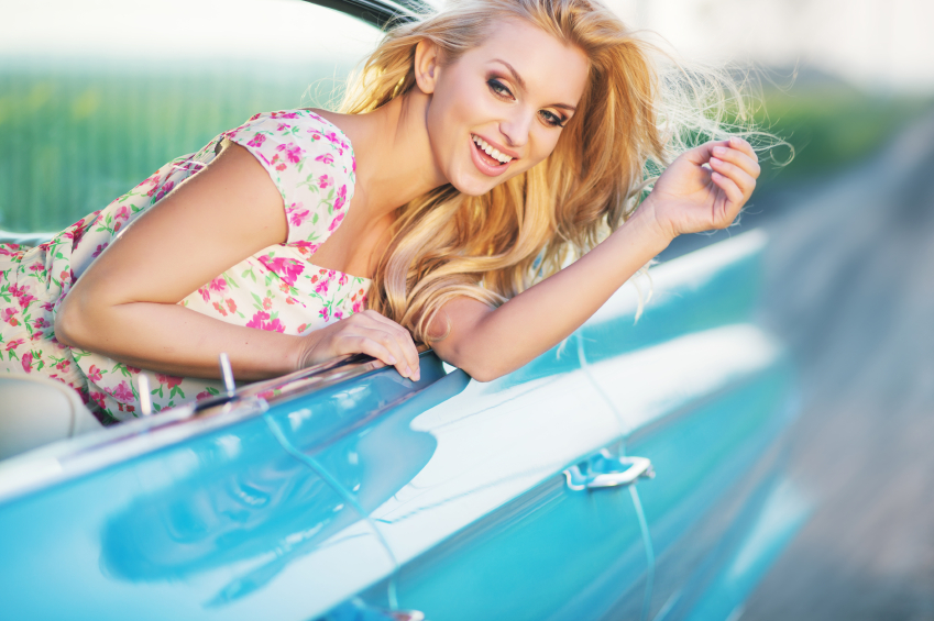 Attractive blonde girl riding the blue cadillac